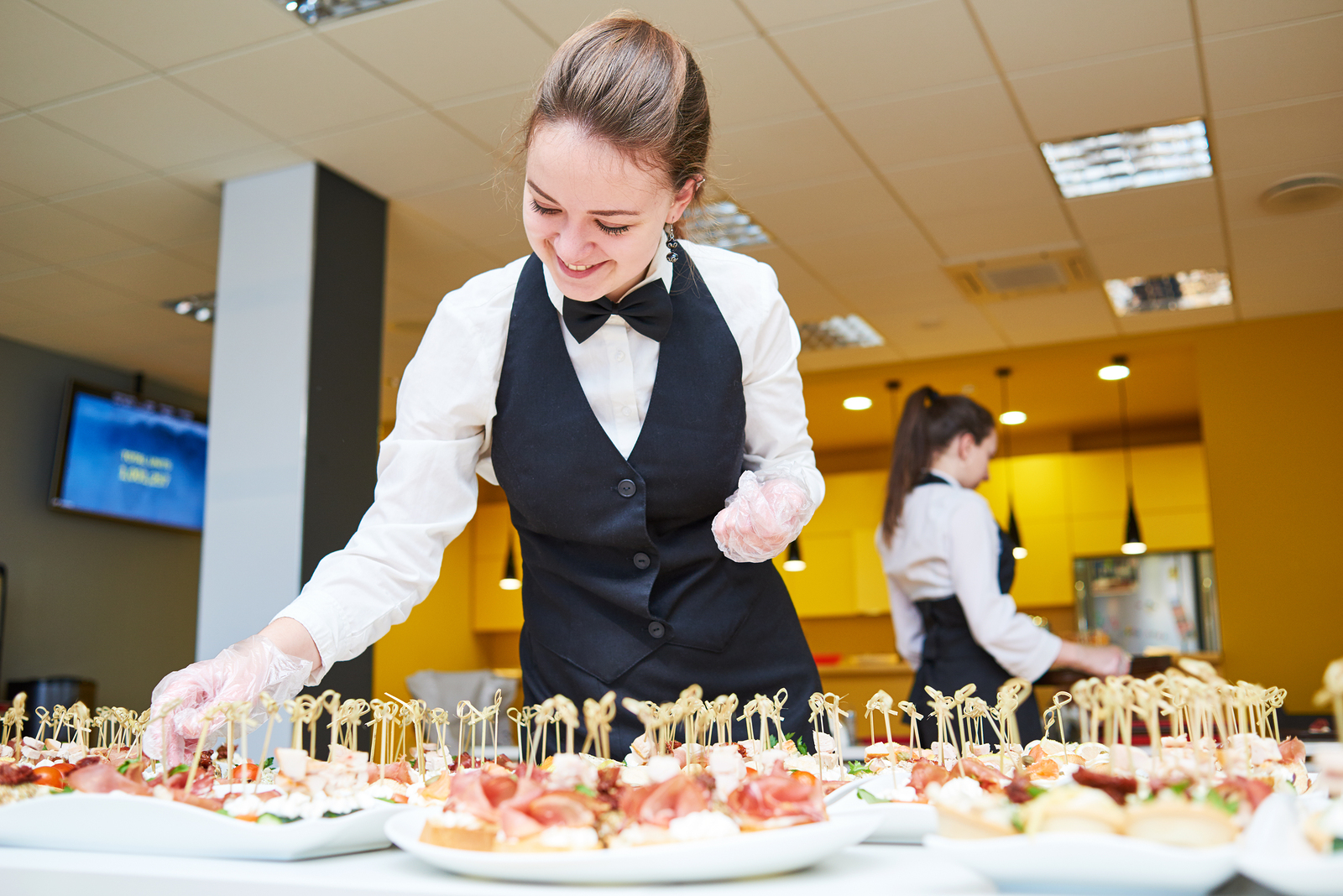 Restaurant waitress serving table with food - Party Staff